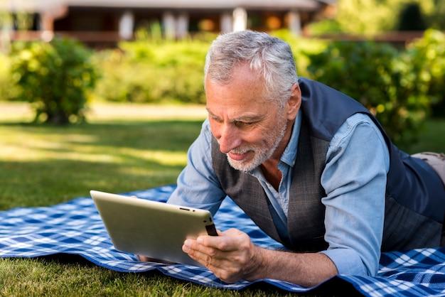 Homem, usando, um, tablete, exterior, tiro médio