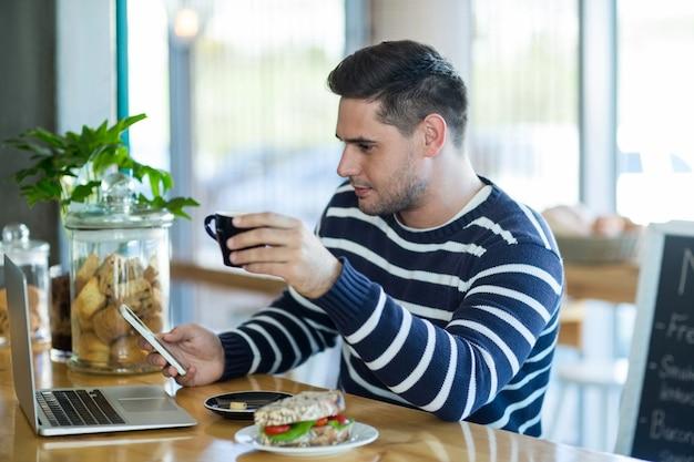 Homem usando um telefone celular enquanto toma café