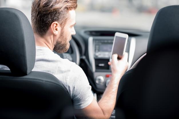Homem usando um telefone inteligente, sentado no banco da frente do carro. visão traseira focada no rosto