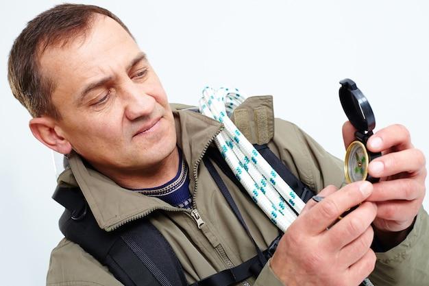 Homem usando uma bússola para encontrar o sentido