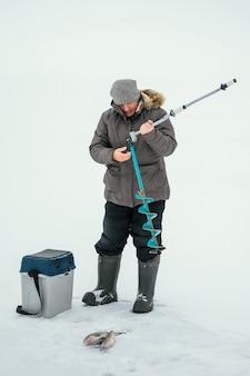 Homem usando uma caixa para o peixe que pescou