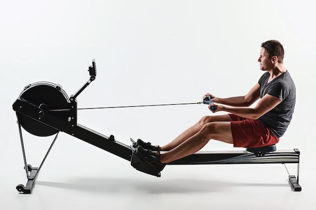Homem usando uma máquina de imprensa em um clube de fitness. jovem fazendo um exercício de pé no simulador. vista lateral