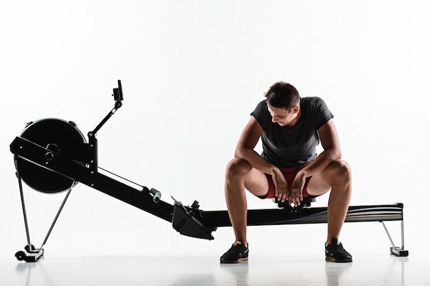 Homem usando uma máquina de imprensa em um clube de fitness.