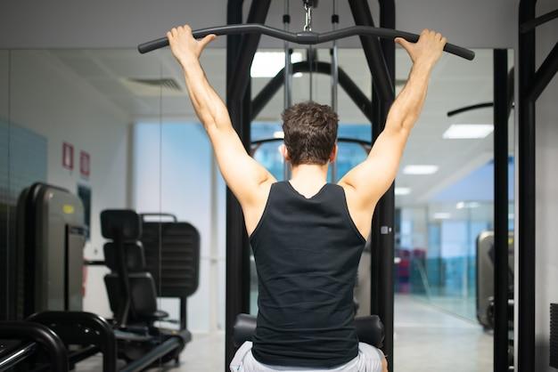 Homem usando uma máquina de lat em uma academia para treinar seus ombros e costas