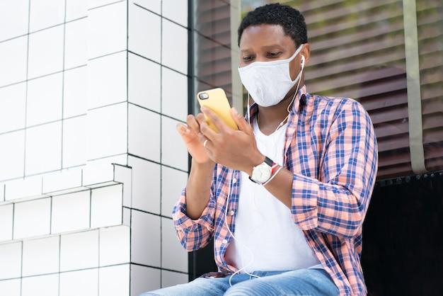 Homem usando uma máscara facial e usando seu telefone celular enquanto está sentado em uma vitrine na rua