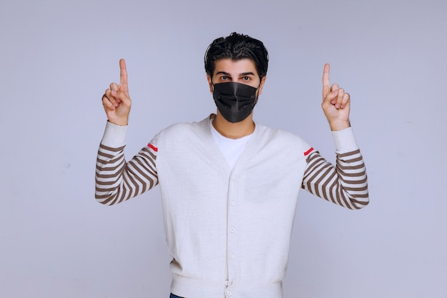 Homem usando uma máscara preta apontando para algum lugar.
