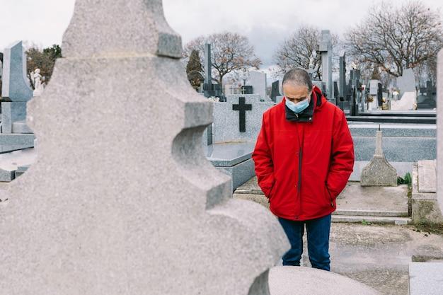 Homem usando uma máscara, triste e orando, em frente ao túmulo de um parente falecido nos tempos de covid-19