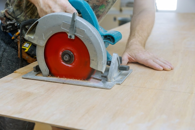 Homem usando uma serra circular para cortar madeira compensada na fábrica de produção de madeira