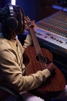 Homem usando violão para escrever uma nova música