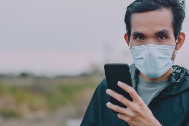 Homem usar máscara facial médica e jogar no celular inteligente