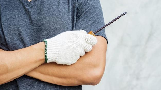 Homem usar uma luva e segurando a chave de fenda.