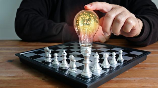 Homem usou o dedo indicador tocando uma lâmpada no conceito de ideia de jogo de tabuleiro de xadrez