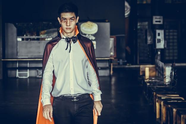 Homem vampiro com sangue em uma fantasia preta de halloween. conceito de halloween.