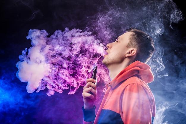 Homem vaping segurando um mod. uma nuvem de vapor. fundo azul escuro.