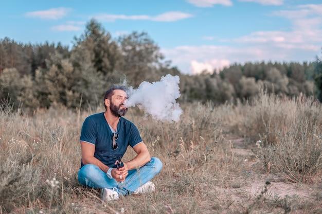 Homem vaporizador libera nuvem de vapor na grama da floresta