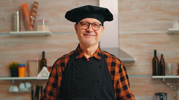 Homem velho caucasiano vestindo avental na cozinha de casa, sorrindo para a câmera. padeiro idoso aposentado com bonete preparando ingredientes de pastelaria na mesa de madeira pronta para cozinhar massas, bolos e pão saboroso caseiro.