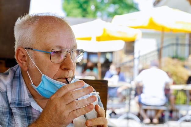 Homem velho com máscara médica a beber água