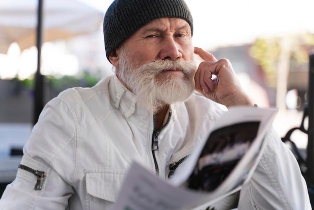 Homem velho com tiro médio e jornal