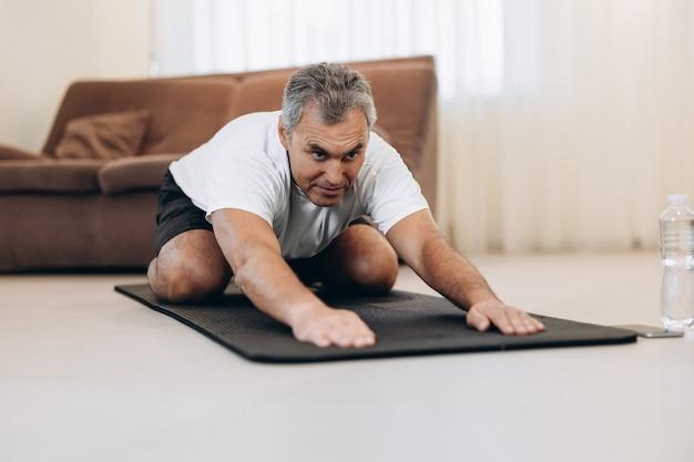 Homem velho em roupas esportivas deitado em colchonetes fazendo asana infantil, exercícios para acalmar o corpo e a mente, esticando as mãos para a frente