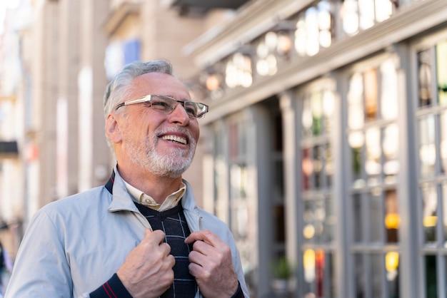 Homem velho feliz ao ar livre em foto média