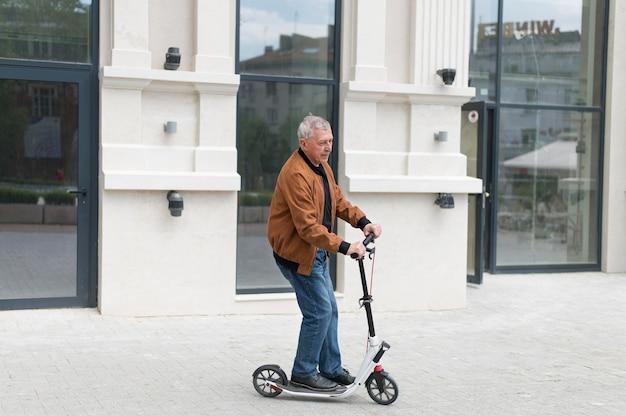 Homem velho na scooter com tiro médio
