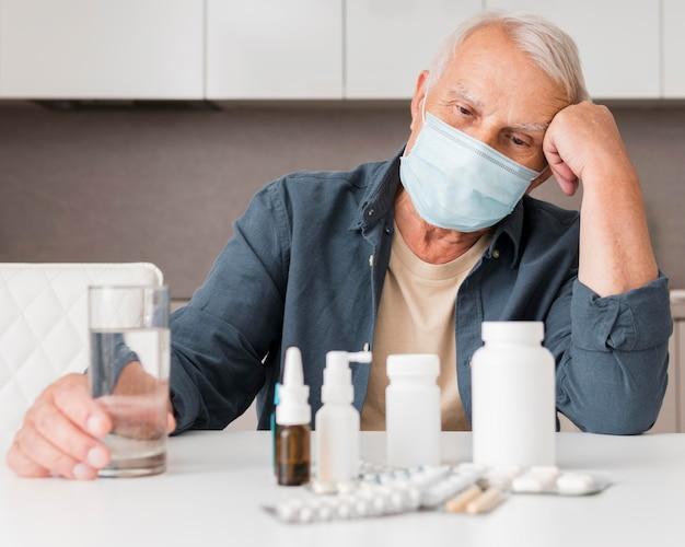 Homem velho olhando um remédio em tiro médio