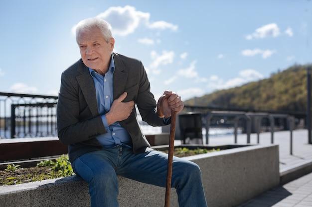 Homem velho, triste e apavorado sentado no canteiro de flores olhando para o horizonte e esperando pelo melhor