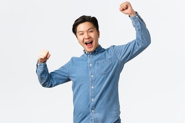 Homem vencedor de sucesso regozijando-se com a vitória, levantando as mãos em um gesto de hooray, dizendo que sim, atingindo a meta, ganhando o prêmio, tornando-se campeão e triunfando sobre boas notícias, fundo branco.