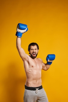 Homem vencedor em luvas de boxe goza de vitória.