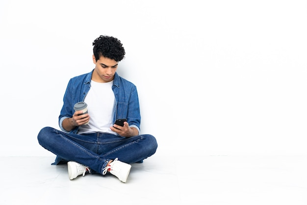 Homem venezuelano sentado no chão segurando café para levar e um celular