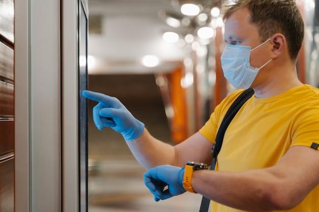 Homem verifica tempo no relógio, usa tela sensível ao toque em luvas protetoras de borracha, evita a disseminação de coronavírus