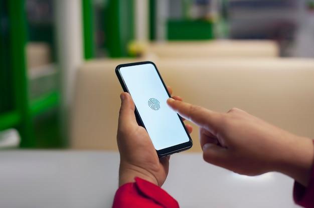 Homem verifica uma impressão digital em seu smartphone. proteja e desbloqueie seu telefone e aplicativos.