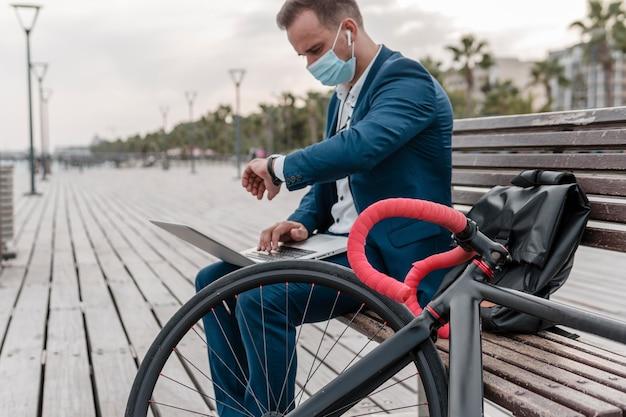 Homem verificando a hora ao lado de uma bicicleta