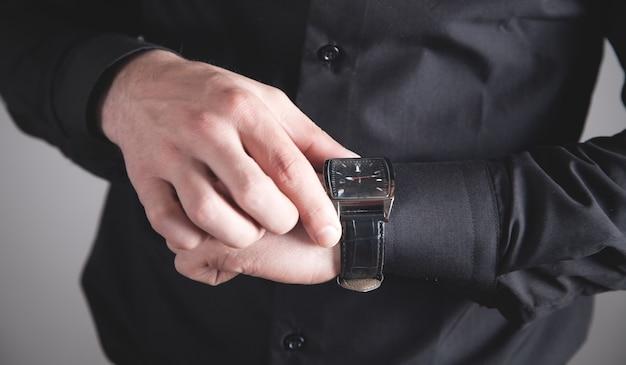 Homem verificando as horas no relógio de pulso.