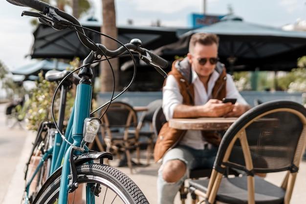 Homem verificando o telefone ao lado de uma bicicleta