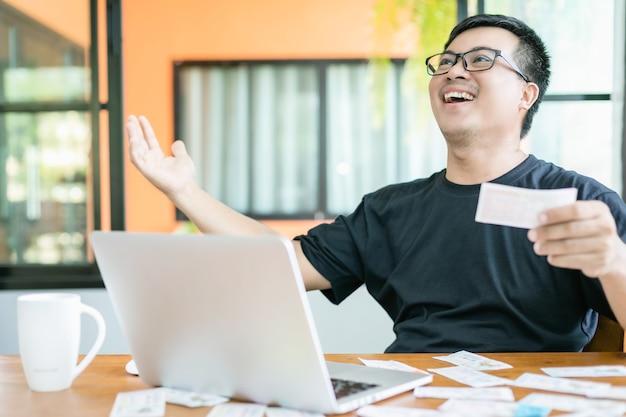 Homem verificando os resultados da loteria no laptop e ganhando