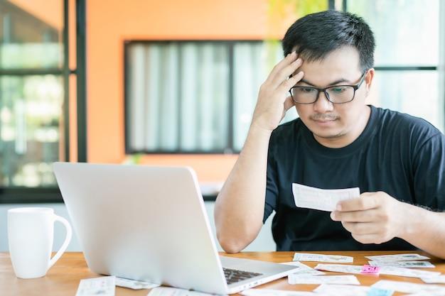 Homem verificando os resultados da loteria no laptop e perdendo