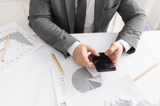 Homem verificando seu telefone no trabalho