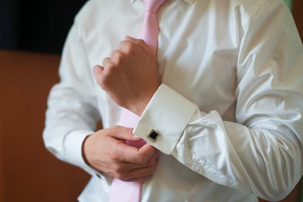 Homem veste as algemas da camisa noivo da manhã acessórios