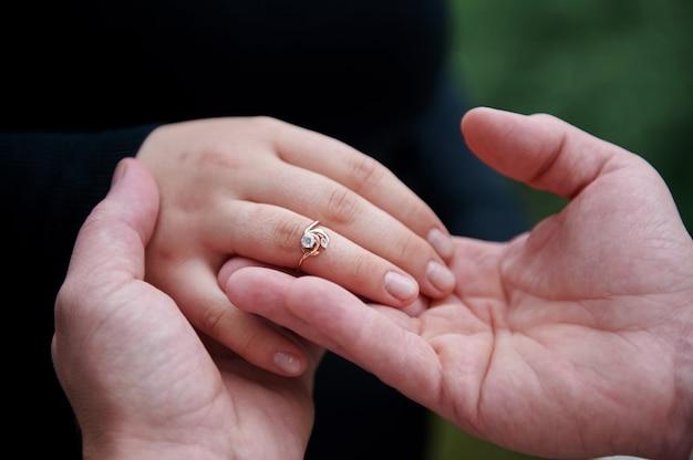 Homem veste um anel de noivado em um dedo de mulher