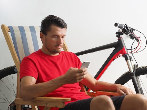 Homem vestido camiseta vermelha em auto-isolamento, senta-se na cadeira perto de bicicleta, quarentena em casa. olha para o telefone. estilo de vida.
