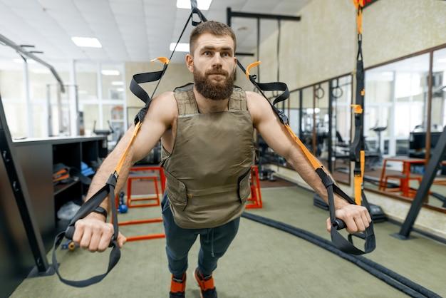 Homem vestido com colete blindado ponderado militar, fazendo exercícios