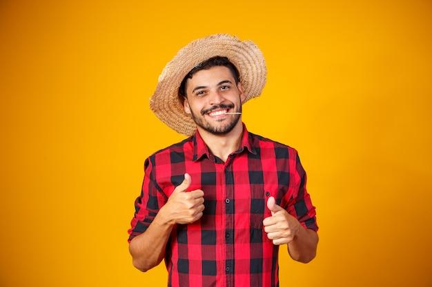 Homem vestido com roupa de festa junina com polegar para cima fazendo sinal de ok