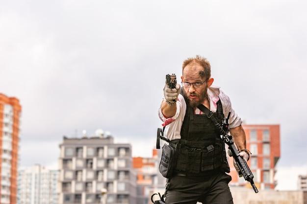 Homem vestido com um colete à prova de balas, uma camisa com sangue, persegue uma vítima com uma arma