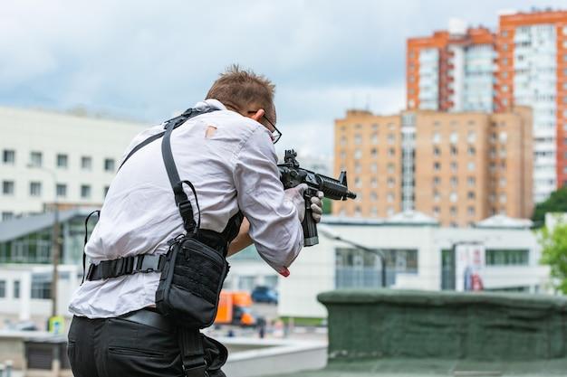 Homem vestido com um colete à prova de balas, uma camisa no sangue, persegue uma vítima com uma arma. estilo de filme de ação