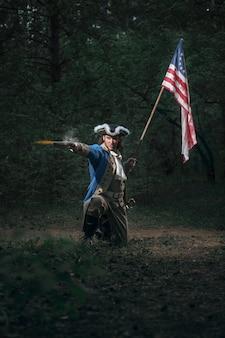 Homem vestido como soldado da guerra da independência dos estados unidos visa pistola com bandeira