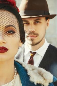 Homem vestido como um gangster está por trás de uma mulher em um chapéu