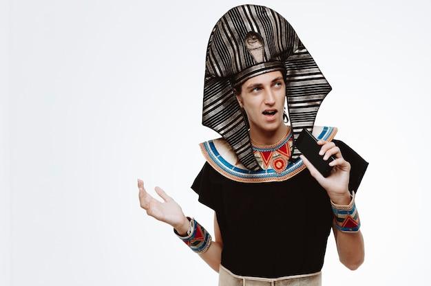 Homem vestido de egípcio antigo cantando uma música usando o smartphone como microfone e se divertindo em branco