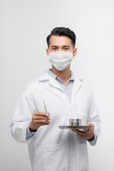Homem vestido de enfermeiro, segurando uma bandeja de remédios e sorrindo