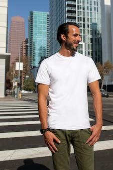 Homem vestido de forma casual cruzando a rua para sessão de fotos ao ar livre